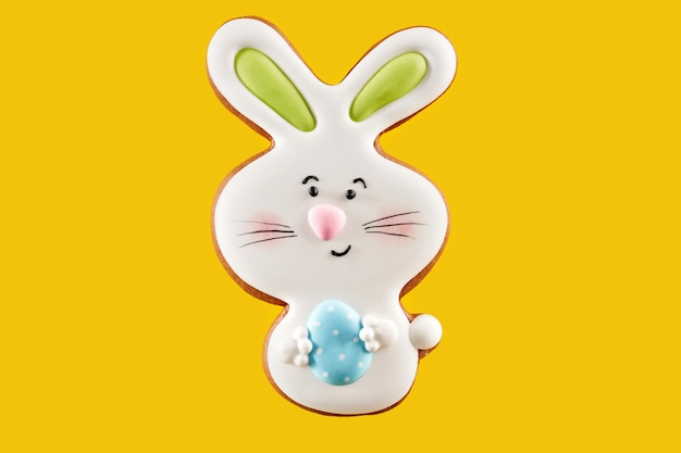 Easter bunny cookie with blue egg over yellow background
