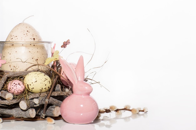 Easter bunny and decorated candlestick in the shape of a nest with quail eggs
