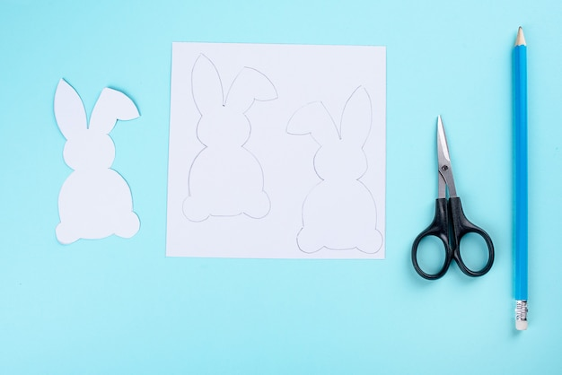 Easter bunny decoration paper cut background. diy holiday handicraft garland of colorful rabbits and craft tools.