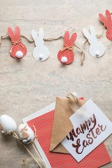 イースターバニー装飾紙カット背景。カラフルなウサギとクラフトツールのdiyホリデー手工芸品の花輪。コピースペースのある上面図