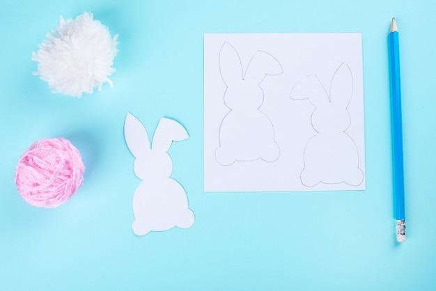 イースターバニー装飾紙カット背景。カラフルなウサギとクラフトツールのdiyホリデー手工芸品の花輪。