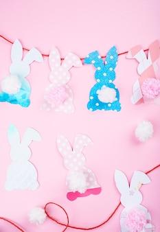 부활절 토끼 장식 종이 잘라 배경. 다채로운 토끼와 공예 도구의 diy 휴일 수공예 화환.