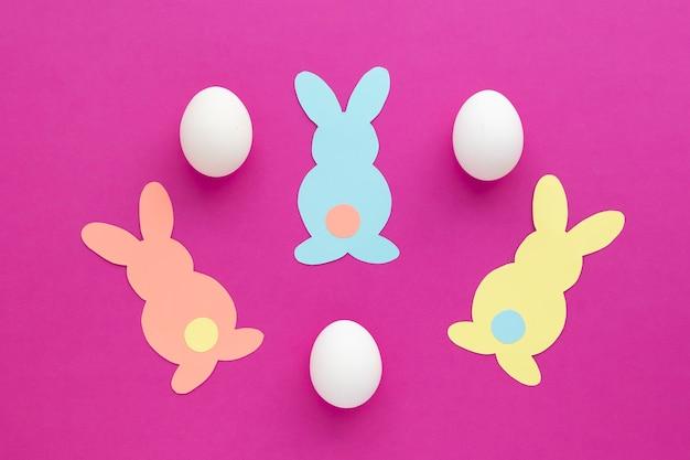 イースターバニーの装飾。ペーパーカットdiyホリデーカラフルなウサギと白いイースターエッグ。上面図、ピンクの背景にスペースをコピーします。