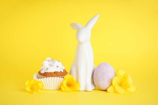 Easter bunny and delicious easter cupcake on yellow background.