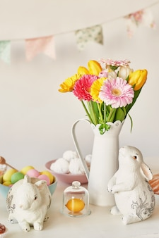 Easter bunny and easter eggs on kitchen table. white rabbit sitting on table with bouquet of tulips and ridge and colorful eggs. easter decoration with rabbit and eggs. easter card template