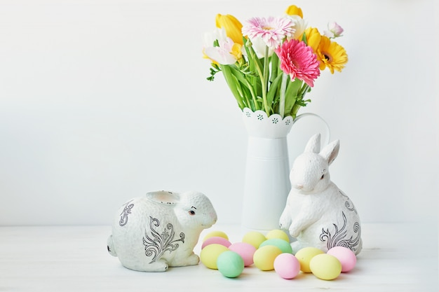 Easter bunny and easter eggs on kitchen table. white rabbit sitting on table with bouquet of tulips and ridge and colorful eggs.
