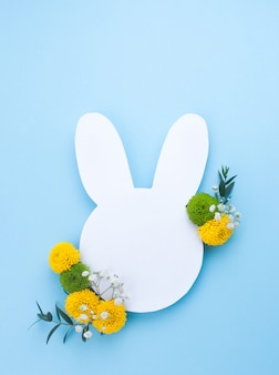 Easter bunny from white paper with flowers on light blue