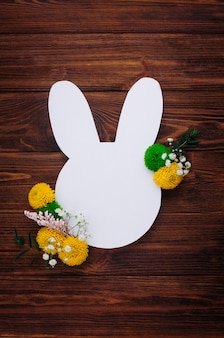 Easter bunny from white paper with flowers on rustic wooden