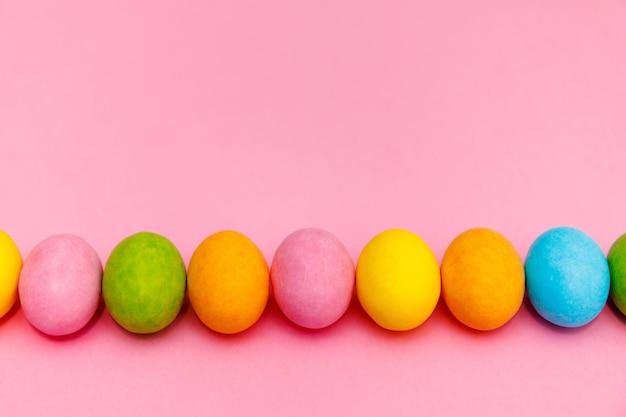 부활절 토끼. 행복 한 부활절 휴일 배경 개념입니다. 플랫 홈 오피스 데스크에서 현대 소박한 핑크 파스텔 종이에 축 하 액세서리와 함께 화려한 토끼 계란을 누워.