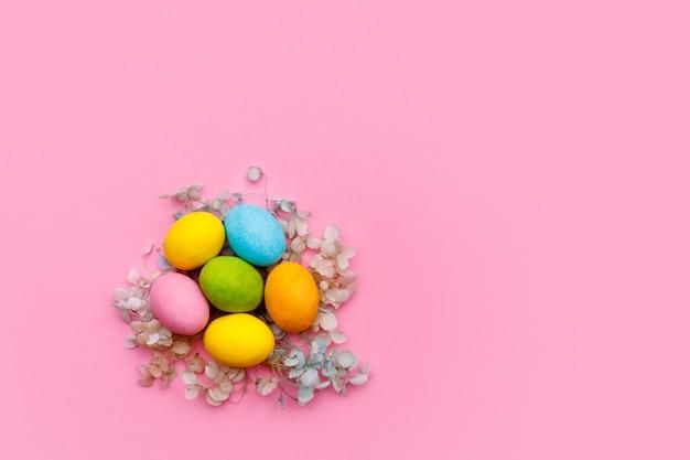 イースターのウサギ。ハッピーイースターホリデーの背景のコンセプト。フラットは、ホームオフィスのデスクでモダンな素朴なピンクのパステル紙にお祝いのアクセサリーとカラフルなバニーエッグを置きます。