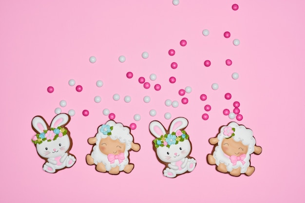 Easter bunny and lamb cookies over pink pastel background
