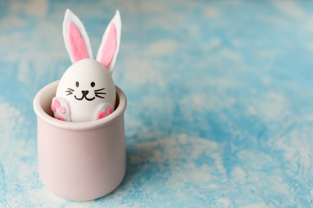 Пасхальный кролик из яйца в розовой чашке на синем фоне.