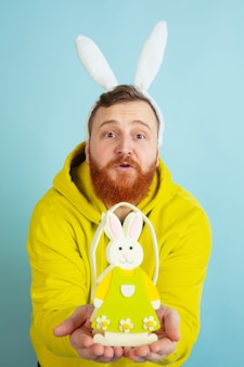 Easter bunny man with bright emotions on blue studio background