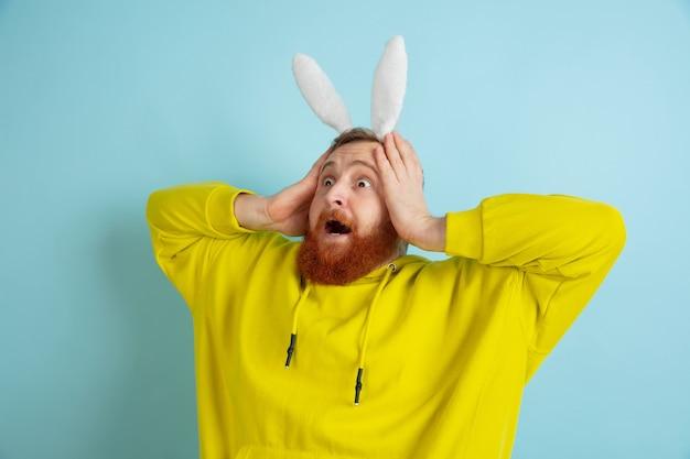 Uomo del coniglietto di pasqua con emozioni luminose su sfondo blu studio