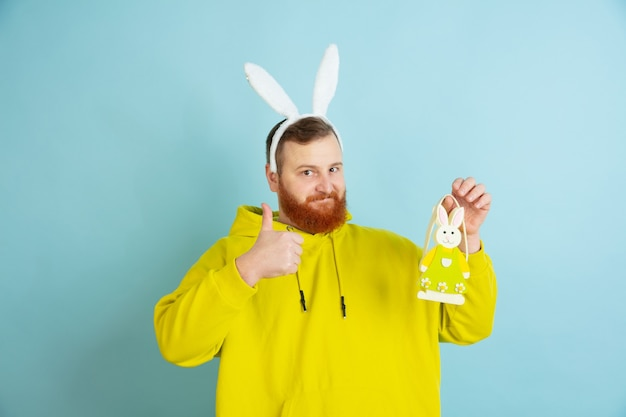 Easter bunny man with bright emotions on blue wall