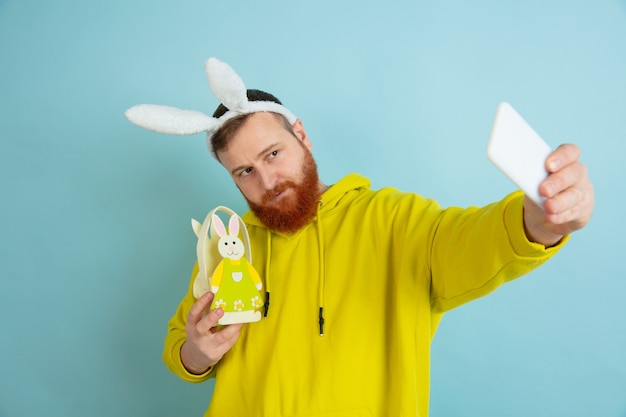 Easter bunny man with bright emotions on blue