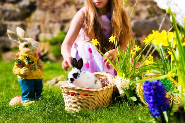 Easter bunny on meadow with basket and eggs