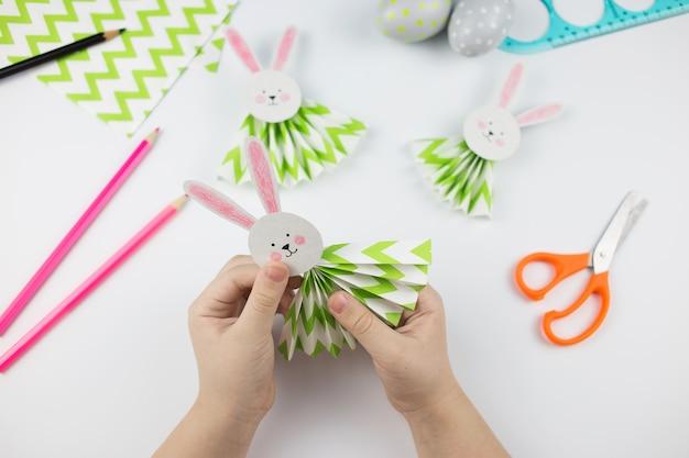 紙切れのイースターバニー。ステップバイステップでdiy。子供のための工芸品のコンセプト。