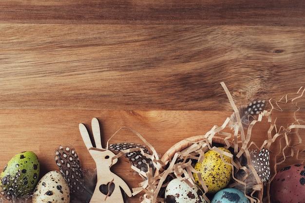 イースターバニー、塗装されたウズラの卵、羽、木製の背景に干し草、フラットレイアウト、上面図。レトロなスタイルのイースターの装飾。イースターの伝統的な背景。
