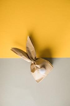 Пасхальный кролик бумажное подарочное яйцо, упаковывая идею diy на красочном фоне. минимальная пасхальная концепция, плоская планировка, копия пространства