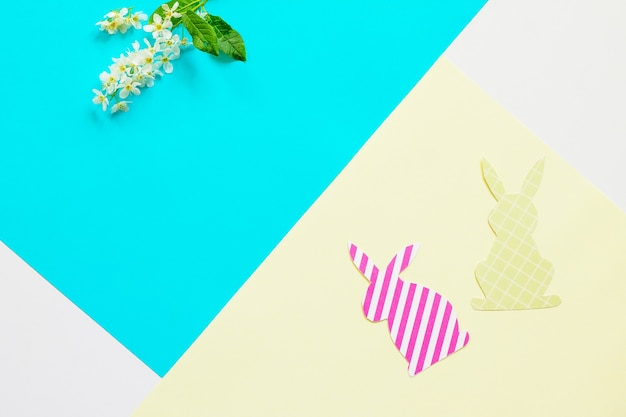 Easter bunny paper and spring flowers minimal easter concept top view flat lay copy space