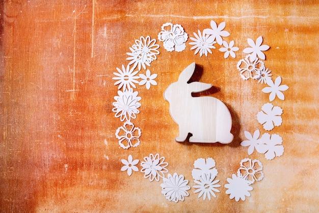 オレンジ色の石の壁の周りにさまざまな紙の花を持つイースターバニーウサギ。フラットレイ、コピースペース。イースターホリデー