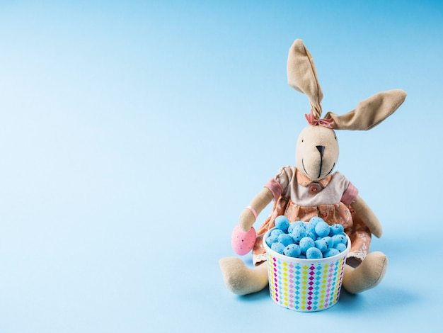 Easter bunny with colorful eggs on blue backdrop