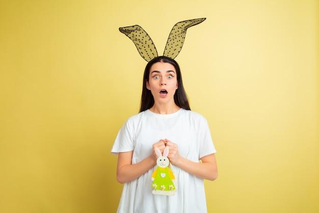 Пасхальный кролик женщина с яркими эмоциями на желтом