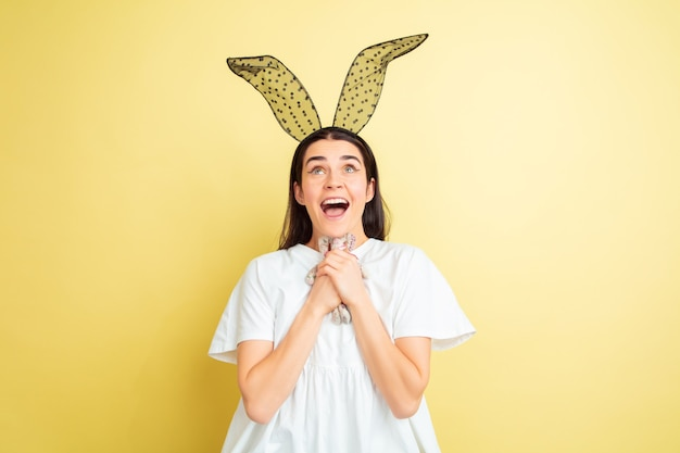 Easter bunny woman with bright emotions on yellow studio