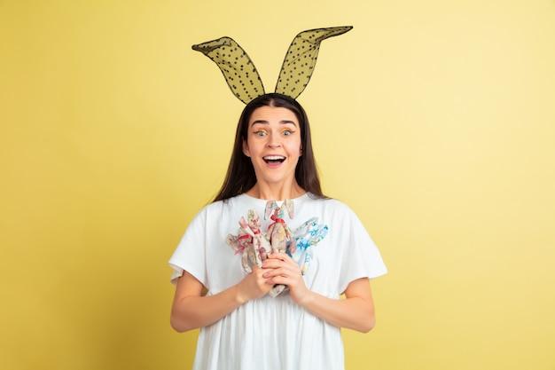 Donna del coniglietto di pasqua con emozioni luminose sulla parete gialla