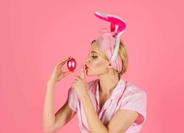 ウサギの耳を持つイースターバニーの女性。イースターエッグ。