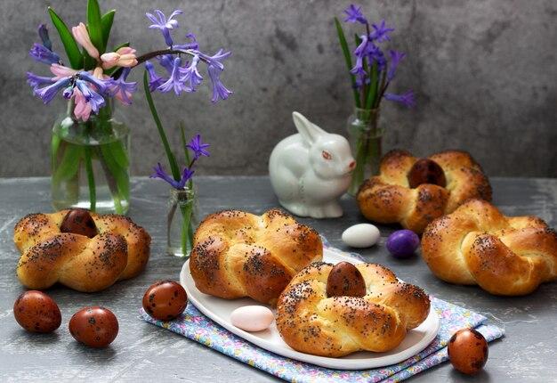 イースターのパン、着色された卵、灰色のコンクリート背景に花。