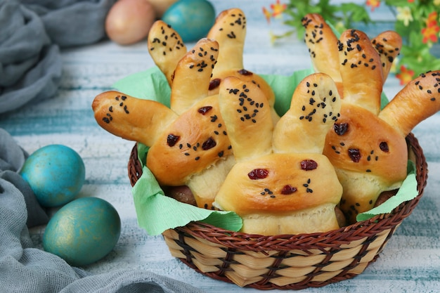Easter buns in the form of hares with multi-colored eggs are located in a wicker basket on a blue surface, culinary idea for children, closeup