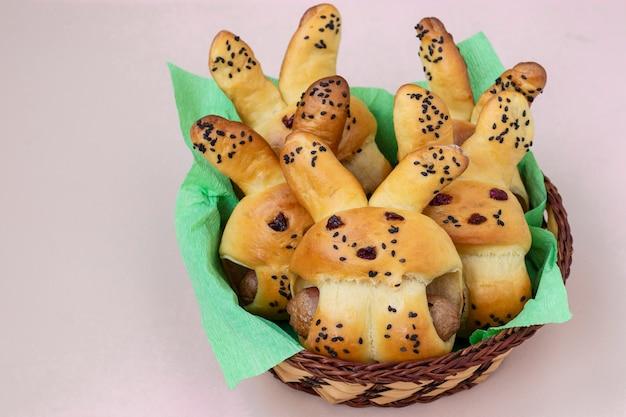 Пасхальные булочки в виде зайцев расположены в плетеной корзине на светлой поверхности, кулинарная идея для детей, крупным планом