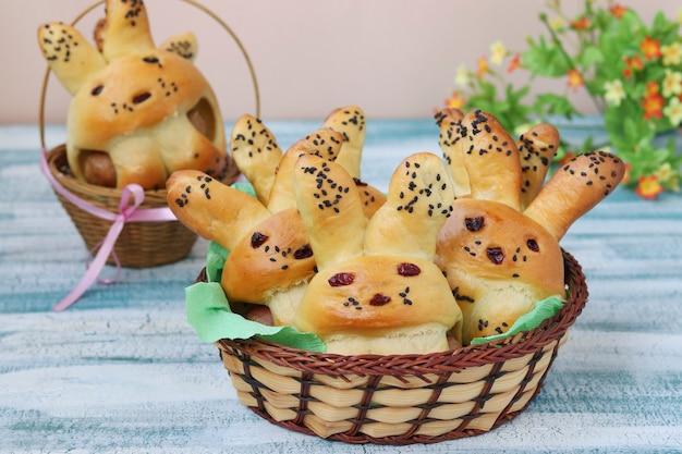 ウサギの形のイースターパンは、青い背景の籐のバスケット、子供のための料理のアイデア、クローズアップに位置しています