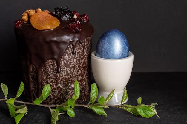 黒の背景にイースターケーキと色の卵。休日の食べ物とイースターのコンセプト。