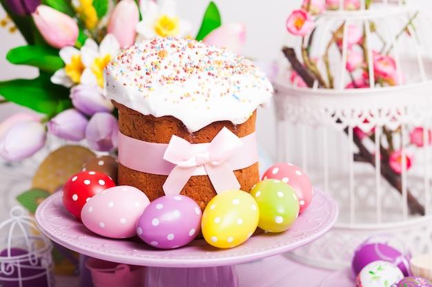 Пасхальный кулич и красочные яйца в горошек на тарелке и цветы на переднем плане