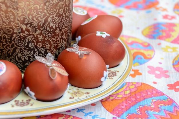 Кулич и украшенные куриные яйца выложены на тарелку. пасхальная традиция: обмениваются куриными яйцами и говорят: «иисус воскрес!» празднование пасхи.