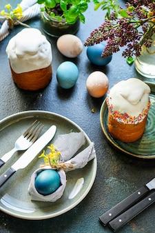 伝統的な装飾とおやつを設定するイースターケーキとイースターエッグのお祝いテーブル