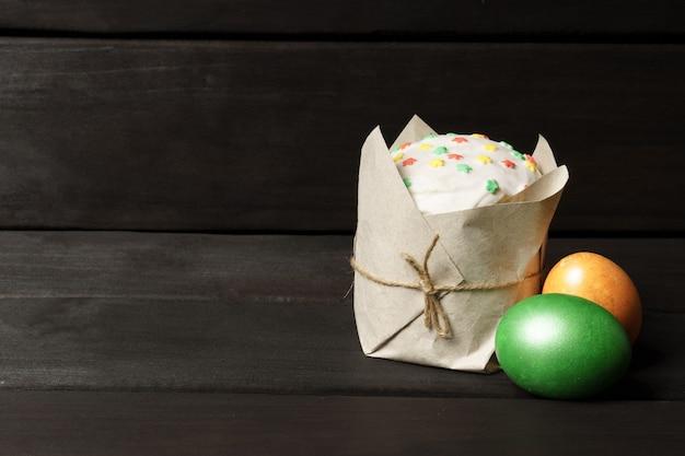 Кулич и два цветных пасхальных яйца на темном деревянном столе