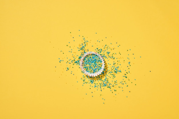 Форма для выпечки куличей с конфетой и разбросанной кондитерской заправкой на желтом фоне.