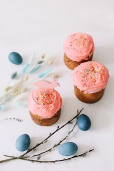 밝은 배경에 부활절 케이크, 다채로운 계란과 버드 나무 가지
