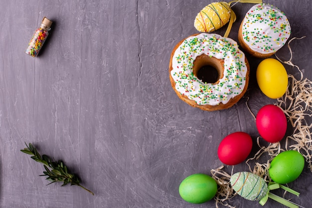 Easter cake and colorful eggs on a dark background