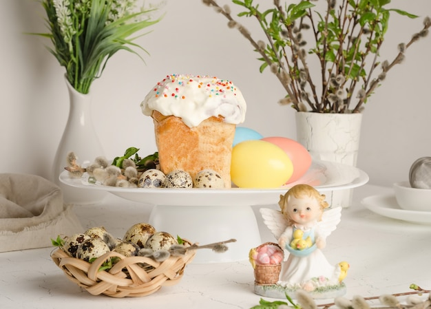 Easter cake and colorful eggs on a festive easter table with pussy willow and angel figurine