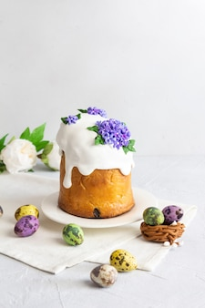 Easter cake colorful eggs and flowers composition on white background