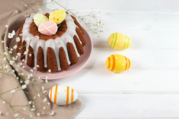 Easter cake and colorful eggs on a white wooden background
