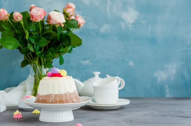 Пасхальный кулич. творожная пасха пасха три шоколадных конфеты с кокосом и конфетными яйцами сверху на белой тарелке на бетонном фоне с цветами. горизонтальная ориентация. скопируйте пространство.