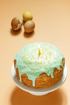 Easter cake covered with icing on a cake bowl and easter eggs. festive concept, selective focus.