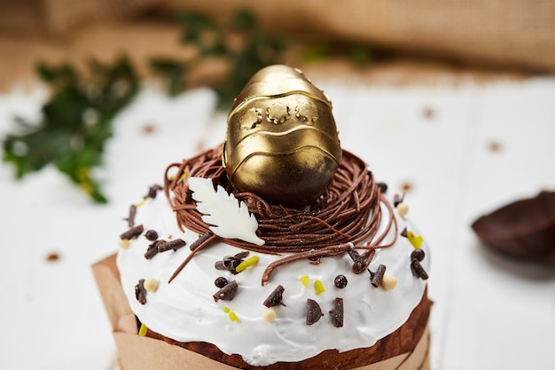 Easter cake decorated by golden chocolate egg on white wooden background, traditional kulich, paska  ready for celebration