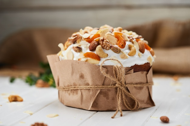 Easter cake decorated by nuts and dried fruits on white wooden background, traditional kulich, paska  ready for celebration